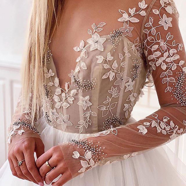 Detail photo of bride wearing long sleeve couture bridal dress.